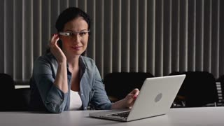 Businesswoman at the desk using laptop and smart glasses