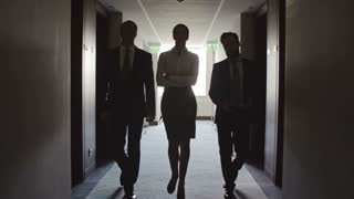 Businesswoman walking towards the camera with two male colleagues through dark corridor in hotel in slow motion