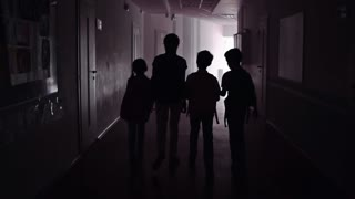 Camera following four outlines of schoolchildren passing through the dark hallway in slow motion