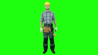 Cheerful workman in hardhat holding paint roller standing on green background and looking at camera
