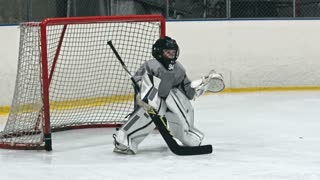 Child playing the position of goalie on an ice hockey team and protecting net from opposing team