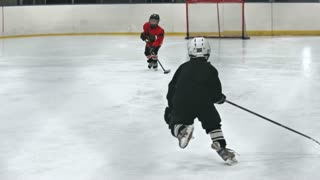 Children in red and black uniform playing professional ice hockey in slow motion