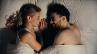 Close-up high angle of beautiful lovers lying in bed, looking at each other and telling sweet words