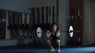 Close up of athletic man performing overhead squats in empty dark gym