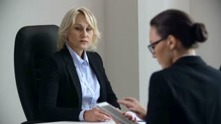 Close up of bossy business woman frowning at her interlocutor sitting with her back to the camera