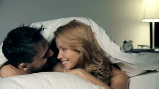 Close up of couple cuddling under the sheets and looking at camera