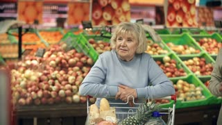 Close up of elderly woman standing in supermarket with shopping cart and waiting for her husband bringing bananas
