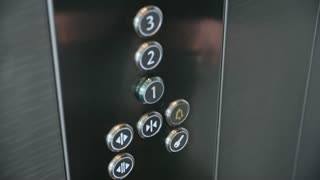 Close-up of forefinger pressing alarm button in office building elevator