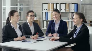 Close up of four young colleagues performing exhilarated dance sitting at the office desk