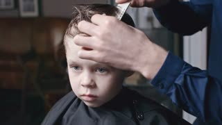 Close up of hands of male hairdresser using comb to brush wet hair of cute little boy in barbershop
