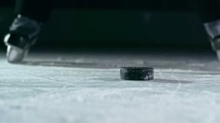 Close-up of hockey puck being struck by hockey player in slow motion