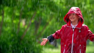 Close up of little boy in raincoat standing in shower