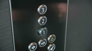 Close up of male hand pushing button on metal panel in the modern elevator