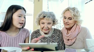 Close up of three generations of women using digital gadget and talking
