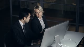 Close up of two coworkers computing in the dark office