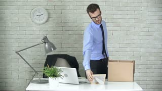 Close up of upset employee packing his things to the dismissal box