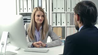 Close up of woman at the office desk talking to man sitting with his back to camera