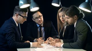Close up of work team of four discussing business in the dark office
