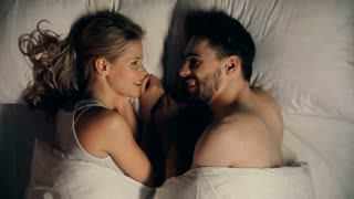 Close up of young couple lying in bed facing each other and talking