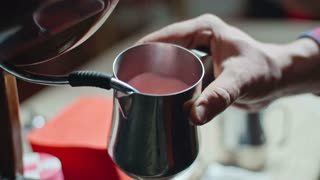 Closeup of coffee shop barista using espresso machine to steam strawberry milk in stainless steel pitcher for latte, slow motion shot on Sony NEX 700