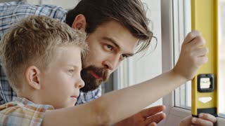 Closeup of man teaching his little son how to use level instrument for home improvement