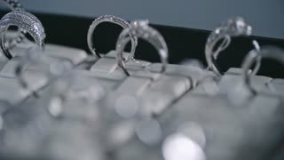 Closeup of shining silver rings with diamonds on tray in jewelry store