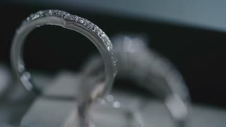 Closeup of two diamond silver rings: one of them embellished with clear crystals and another one with full cut diamond