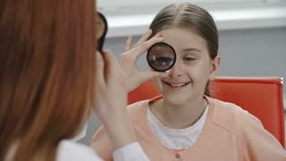 Closeup over the shoulder view of female optometrist examining eyes of little girl through lens