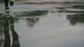 Closeup shot of male legs in sports shoes and tights jogging through puddle in slow motion