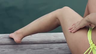 Cropped unrecognizable lady in swimsuit applying sunscreen lotion on her legs