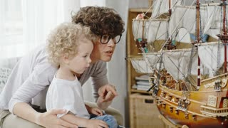 Curly mother and curious toddler boy sitting and looking at ship model