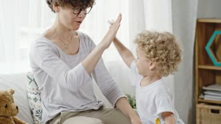 Curly mother in glasses sitting in bed with her toddler boy and teaching him to give high-fives