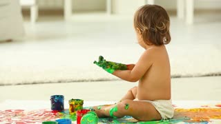 Cute child playing with paints mixing the colors and making a mess