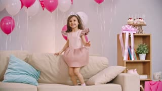 Cute little girl jumping on sofa in the living room decorated for birthday party