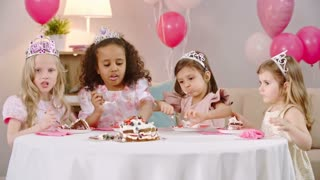 Cute little girls dressed like princesses with whipped cream on their faces enjoying birthday cake at the celebration