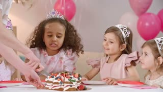Cute little girls sitting at birthday table and looking at fruit cake while mother cutting it with knife