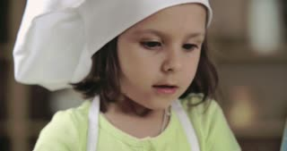 Cute preschoolers tasting sprinkles during baking class