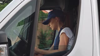 Delivery woman in blue uniform getting out from van, signing application form and walking with package to the house of client