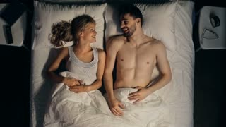 Direct from above view of couple lying in bed and cuddling fondly