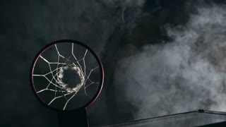Directly above view of basketball player throwing ball into hoop in slow motion in the dark gym with smoke in the air