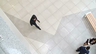 Directly above view of businessman joining his colleagues talking in lobby of business center and greeting them with handshake, slow motion shot on Sony NEX 700