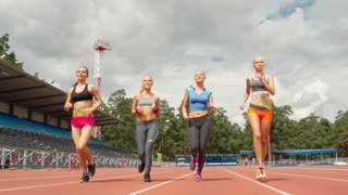 Dolly shot of group of four attractive young women running on track towards the camera in slow motion