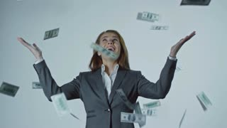 Ecstatic young businesswoman standing isolated on grey background with her hands raised and looking at money falling from above