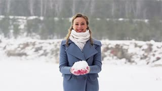 Excited girl having a lot of fun throwing snow on a winter day