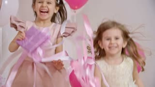 Exhilarated little girls dressed like princesses jumping on couch and holding gift boxes at birthday party in slow motion