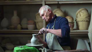 Experienced master doing a clay vase on a pottery wheel