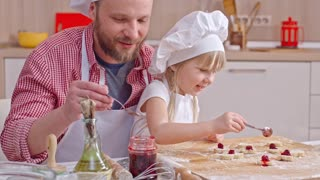 Father and little daughter putting cherries on cookie dough pieces with spoon and talking