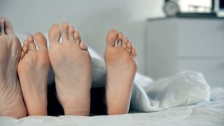 Feet of loving couple lying in bed under white duvet and playing footsie