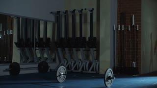 Female bodybuilder working out in dark empty gym