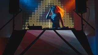 Female DJ playing music and dancing behind decks in dark nightclub